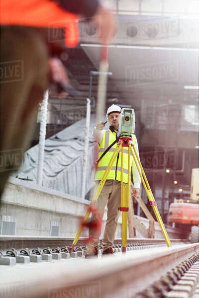 Male engineer using theodolite on tracks at construction site Royalty-free stock photo