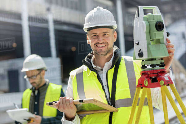 Portrait smiling male engineer using theodolite at construction site Royalty-free stock photo