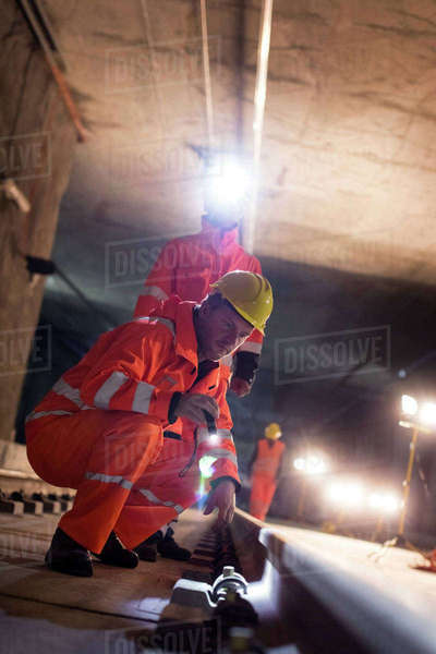 Male construction workers examining underground tracks at dark construction site Royalty-free stock photo