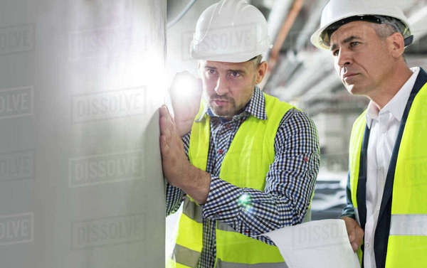 Male engineer with flashlight examining underground wall at construction site Royalty-free stock photo
