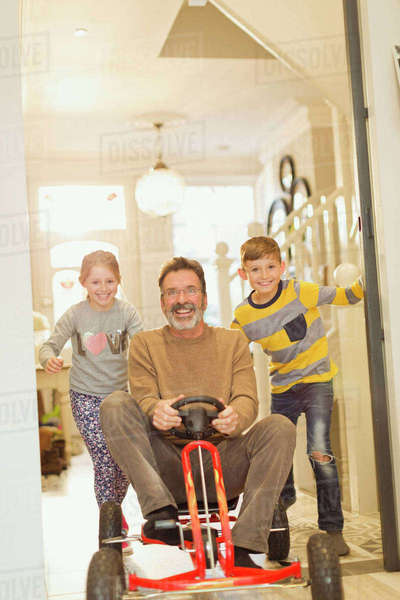 Portrait smiling children pushing father on toy car in foyer corridor Royalty-free stock photo