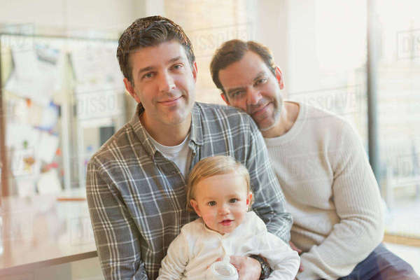 Portrait smiling male gay parents with baby son Royalty-free stock photo