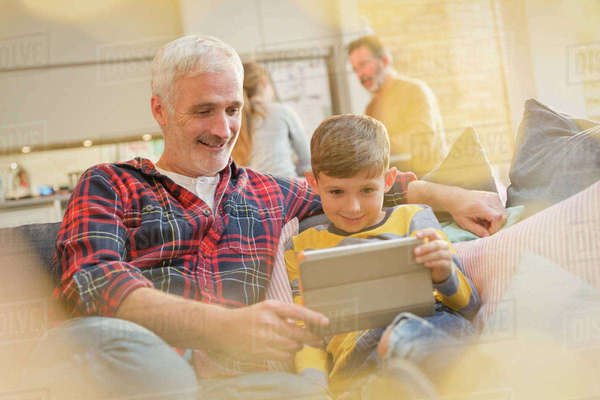 Father and son bonding, using digital tablet on sofa Royalty-free stock photo