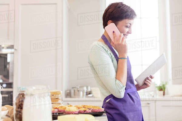 Female caterer baking, talking on cell phone and using digital tablet in kitchen Royalty-free stock photo