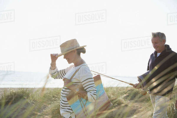 Mature couple with fishing rod walking in sunny summer beach grass Royalty-free stock photo