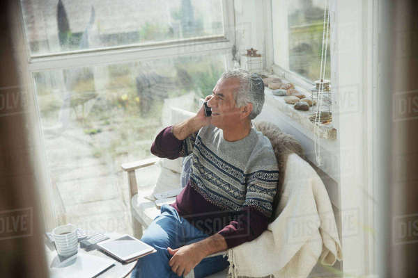 Senior man talking on cell phone on sun porch Royalty-free stock photo