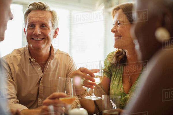 Laughing mature couple drinking wine at restaurant table Royalty-free stock photo