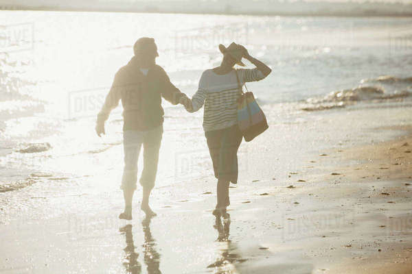 Mature couple holding hands and walking on sunny beach Royalty-free stock photo