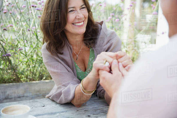 Affectionate mature couple holding hands at patio table Royalty-free stock photo