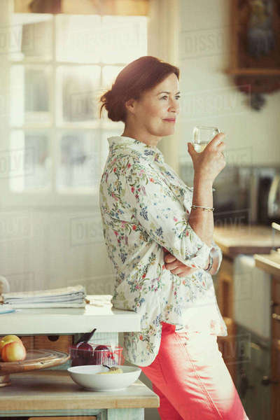 Pensive mature woman drinking wine in kitchen Royalty-free stock photo