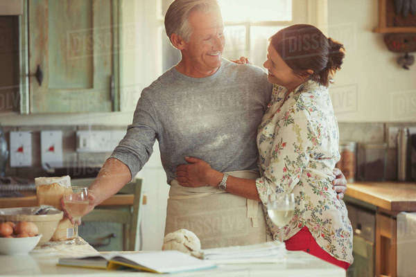 Affectionate mature couple hugging, baking and drinking wine in kitchen Royalty-free stock photo