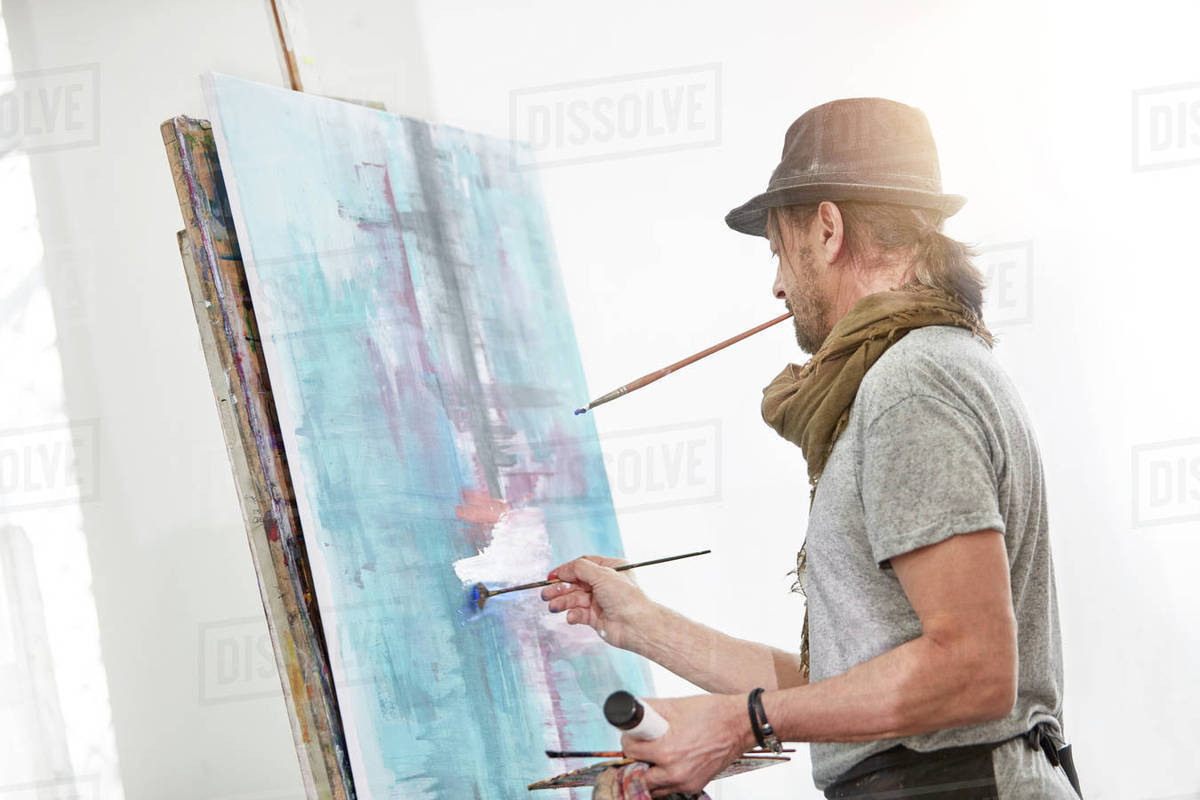 Male Artist Painting At Easel In Art Studio Stock Photo Dissolve