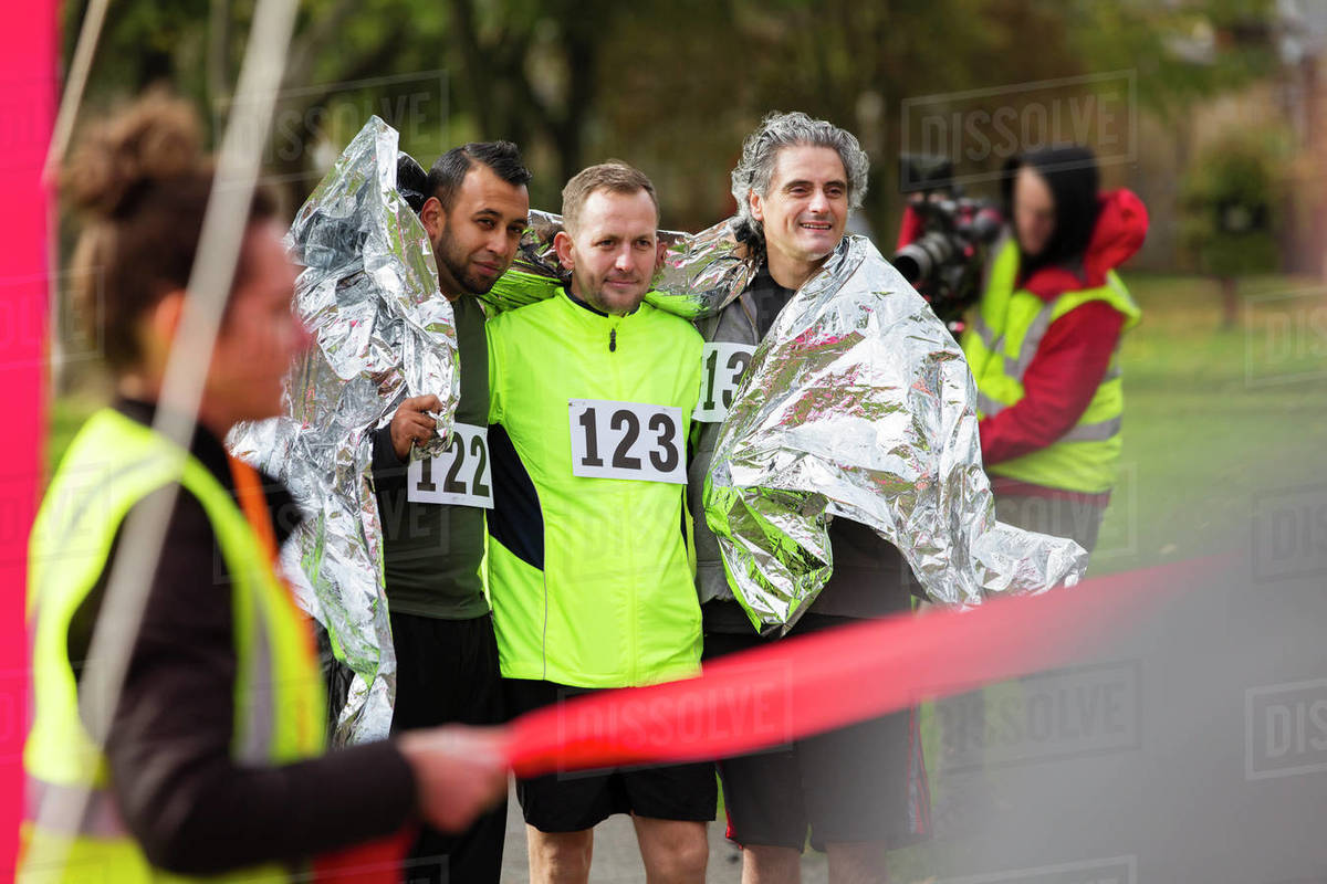 Male Marathon Runners Wrapped In Thermal Blanket At Finish Line