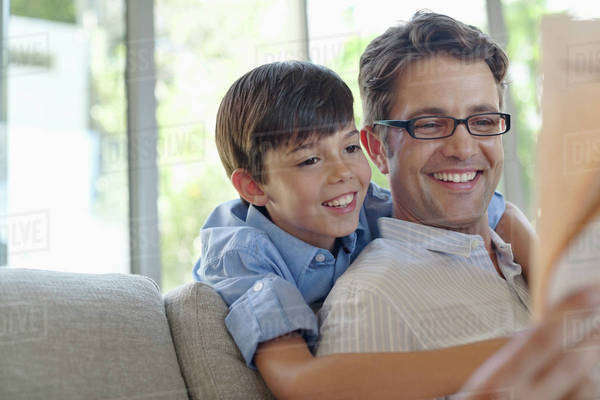 Father and son hugging on sofa Royalty-free stock photo