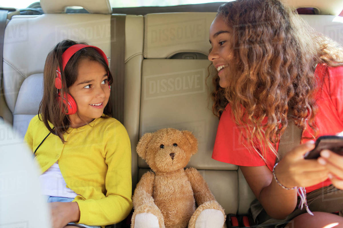 Sisters and teddy bear riding in back set of car Royalty-free stock photo