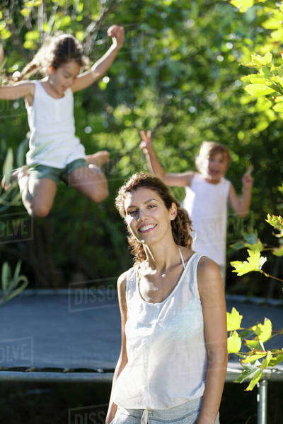 Mother standing by children on trampoline Royalty-free stock photo