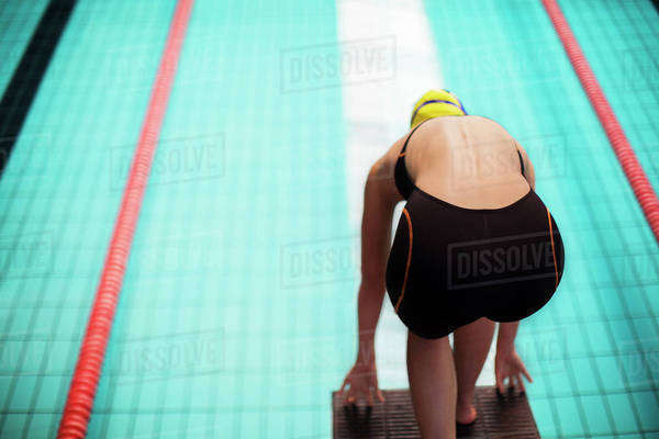 Swimmer poised at starting block above pool Royalty-free stock photo