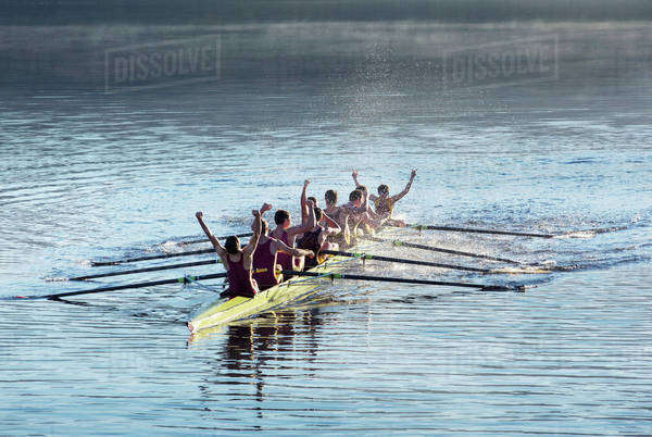 Rowing team celebrating in scull on lake Royalty-free stock photo