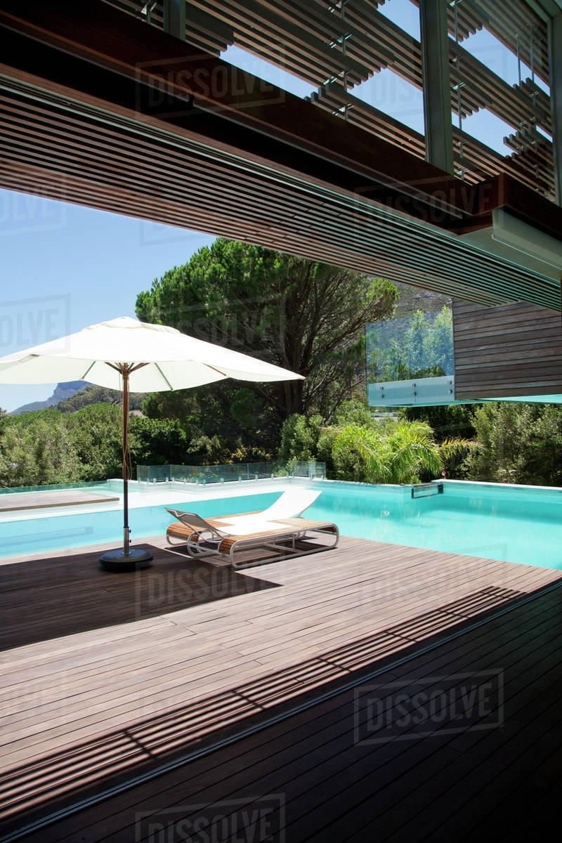 Swimming pool, lounge chair, umbrella stock photo