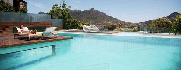 Woman sunbathing on lounge chair next to luxury swimming pool with mountain view Royalty-free stock photo