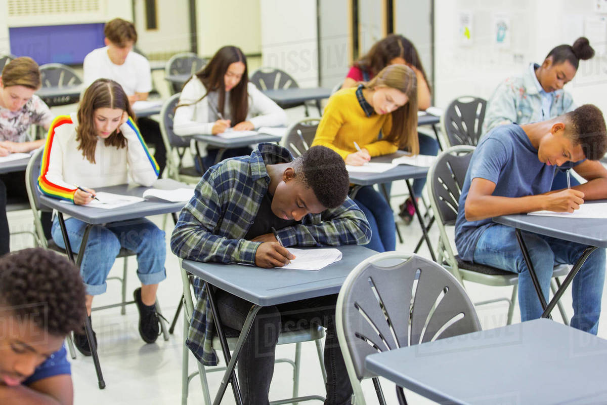 Focused high school students taking exam at desks in classroom Royalty-free stock photo