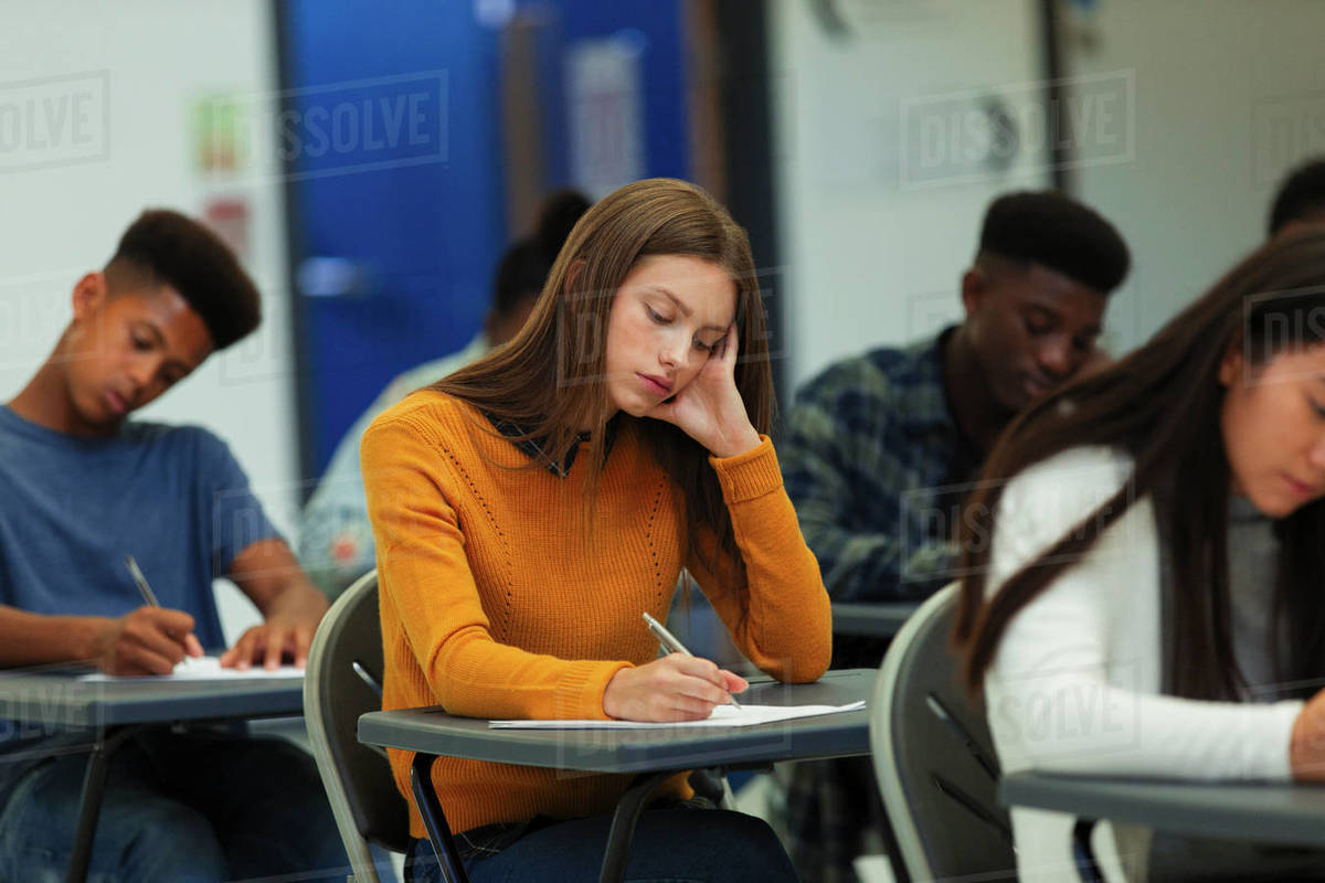 Focused high school girl student taking exam at desk in classroom Royalty-free stock photo