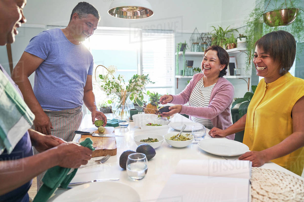 Happy mature couples cooking and eating in kitchen Royalty-free stock photo