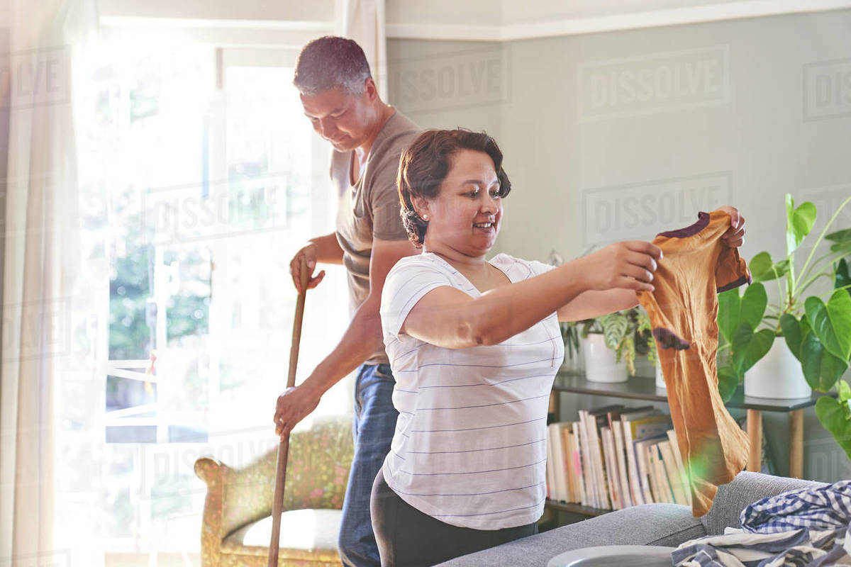 Mature couple folding clothes and sweeping at home Royalty-free stock photo