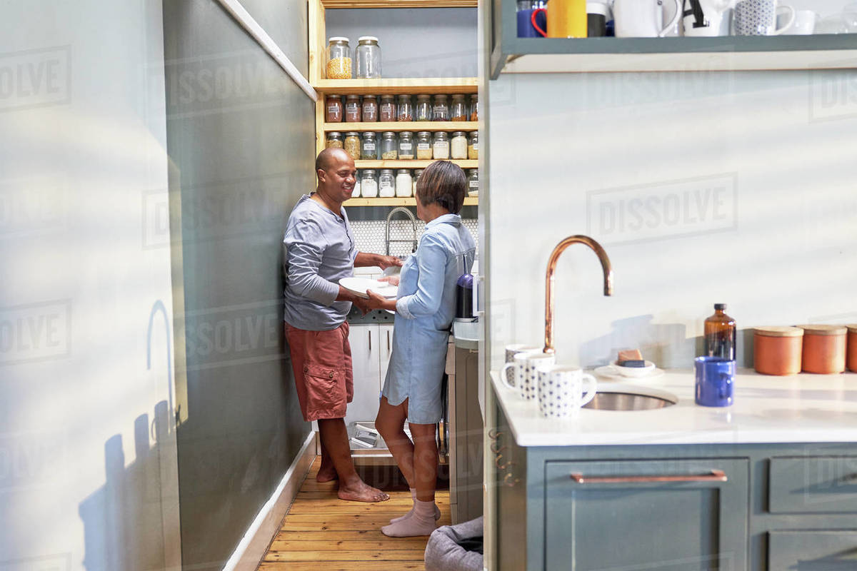Happy couple talking and doing dishes in kitchen Royalty-free stock photo