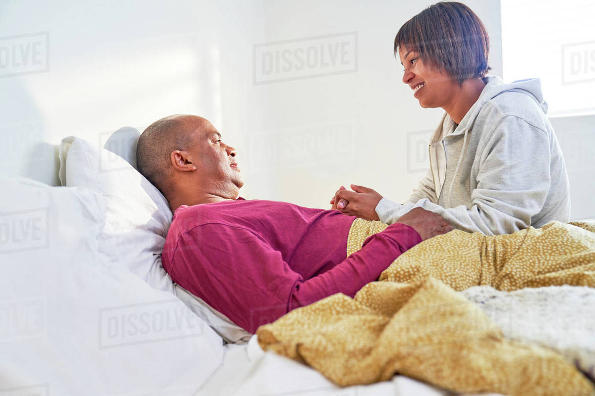 Caring wife checking on sick husband resting in bed Royalty-free stock photo