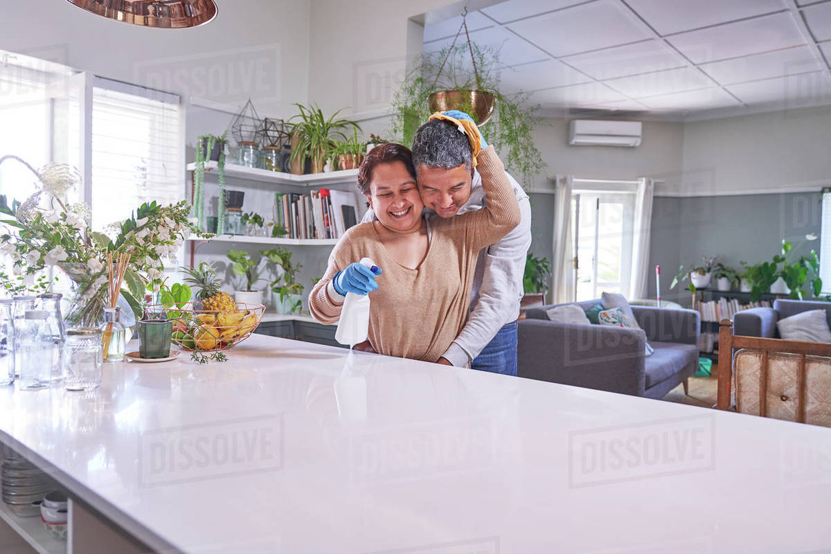 Affectionate mature couple hugging and cleaning kitchen island Royalty-free stock photo