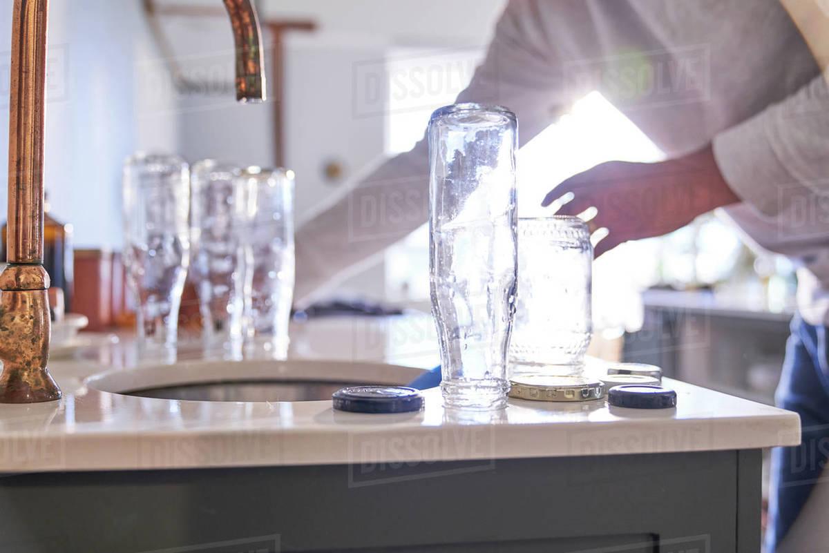 Man washing glass bottles at kitchen sink Royalty-free stock photo