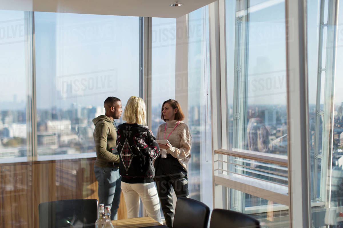 Business people talking at sunny highrise office window Royalty-free stock photo