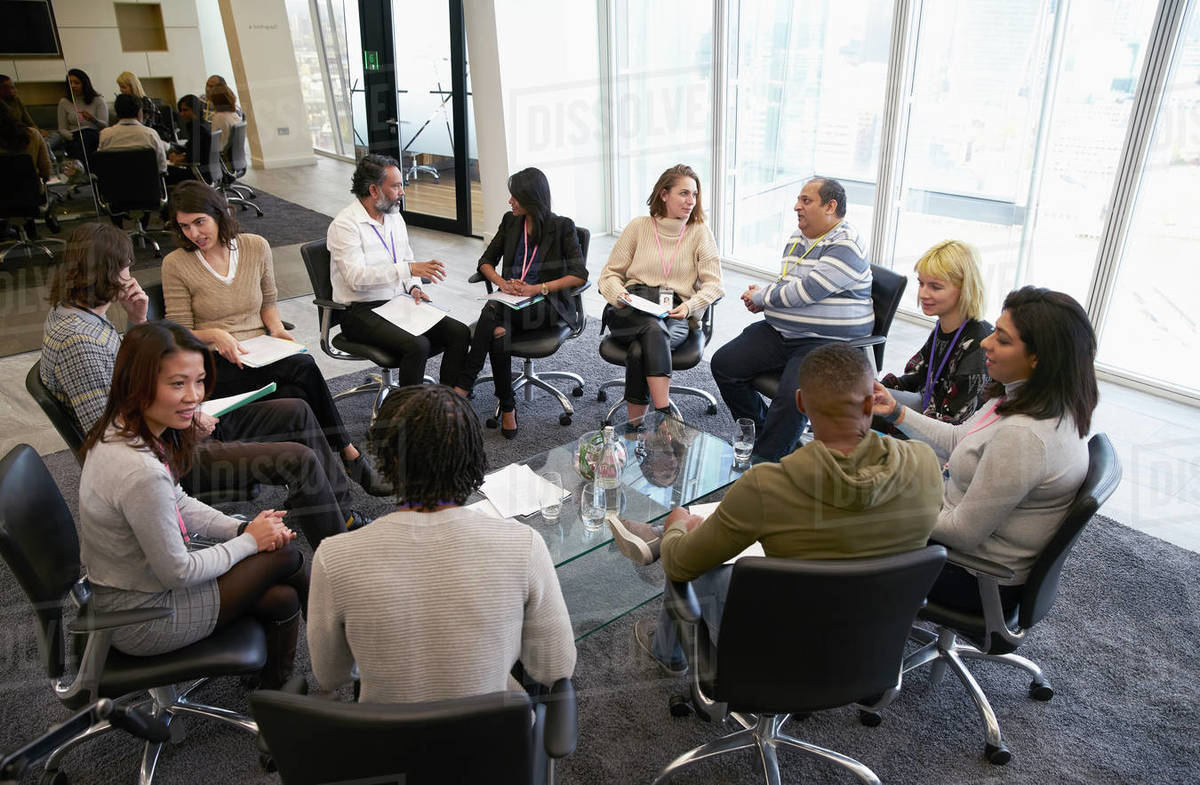 Business people talking in circle in conference room meeting Royalty-free stock photo