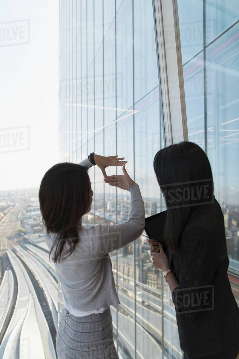 Businesswomen talking at highrise office window Royalty-free stock photo