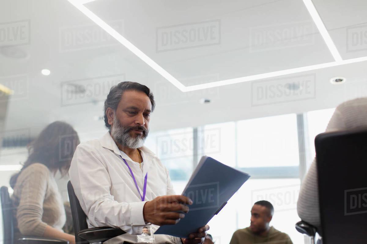 Focused businessman reading paperwork in meeting Royalty-free stock photo