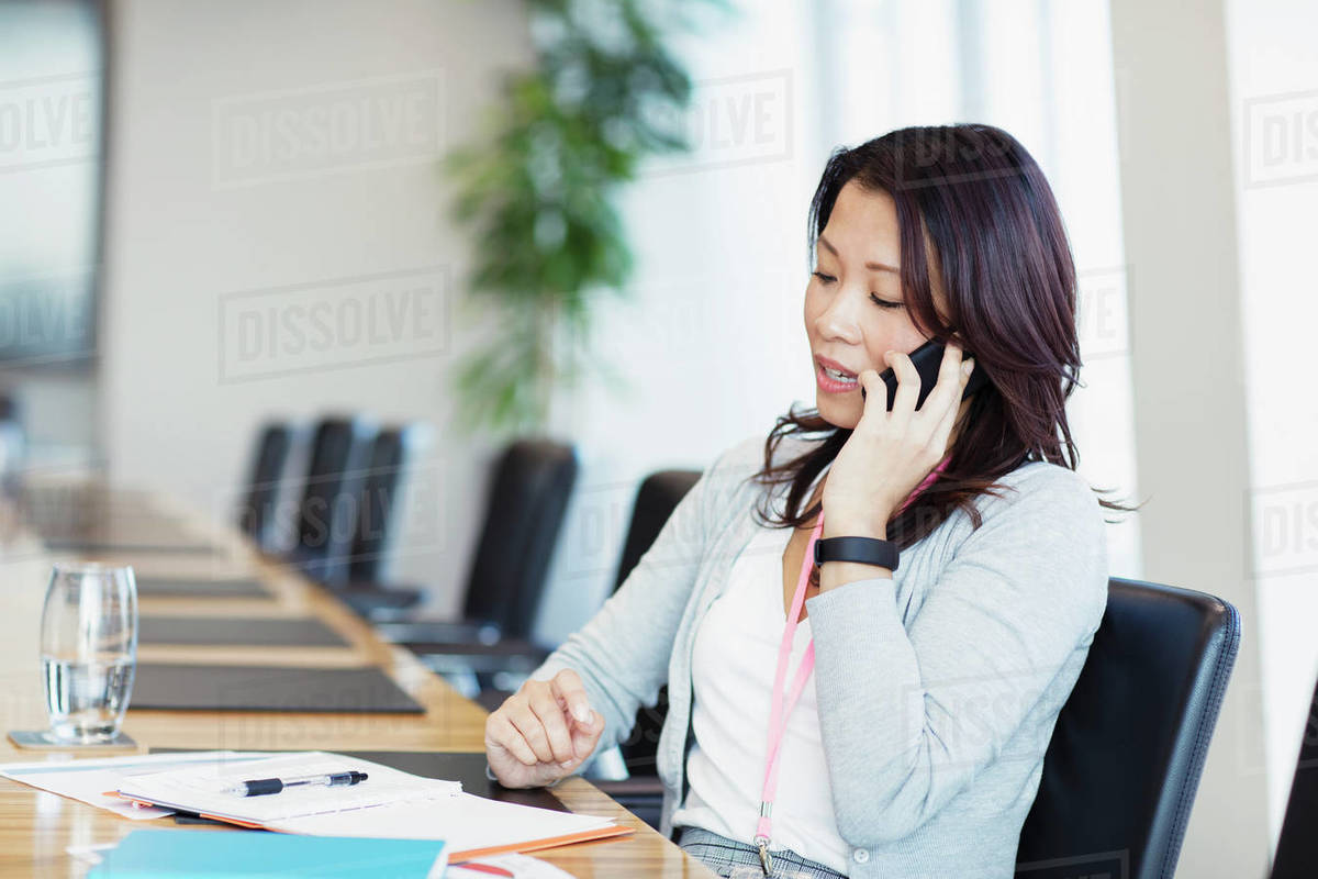 Businesswoman talking on smart phone in conference room Royalty-free stock photo