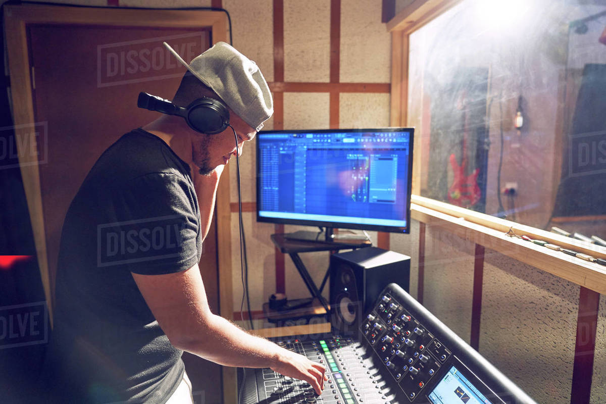 Male music producer working at sound board in recording studio Royalty-free stock photo