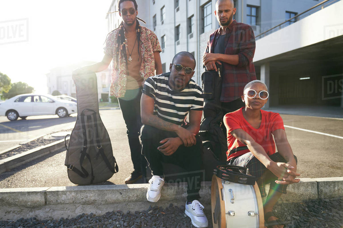 Portrait confident cool musicians in sunny parking lot Royalty-free stock photo