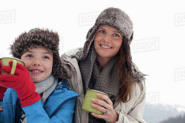 Happy mother and son in fur hats drinking hot chocolate Royalty-free stock photo