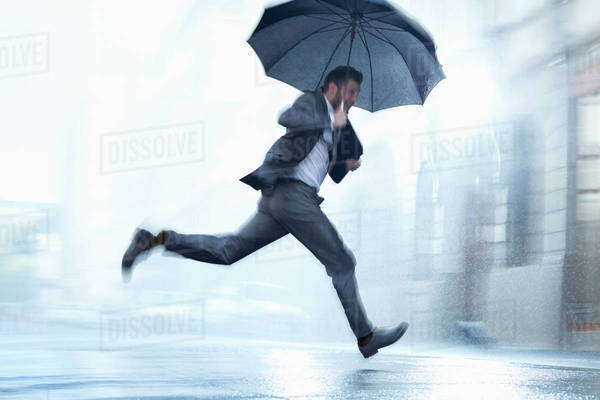 Businessman running with umbrella in rainy street Royalty-free stock photo