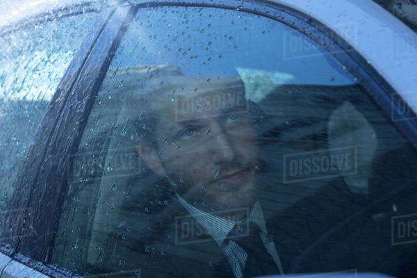 Close up of businessman in car looking up at rain Royalty-free stock photo