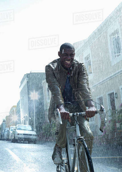 Happy businessman riding bicycle in rain Royalty-free stock photo