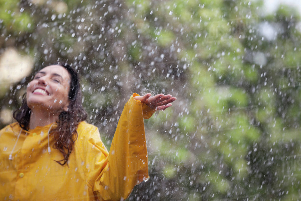 Happy woman standing with arms outstretched in rain Royalty-free stock photo