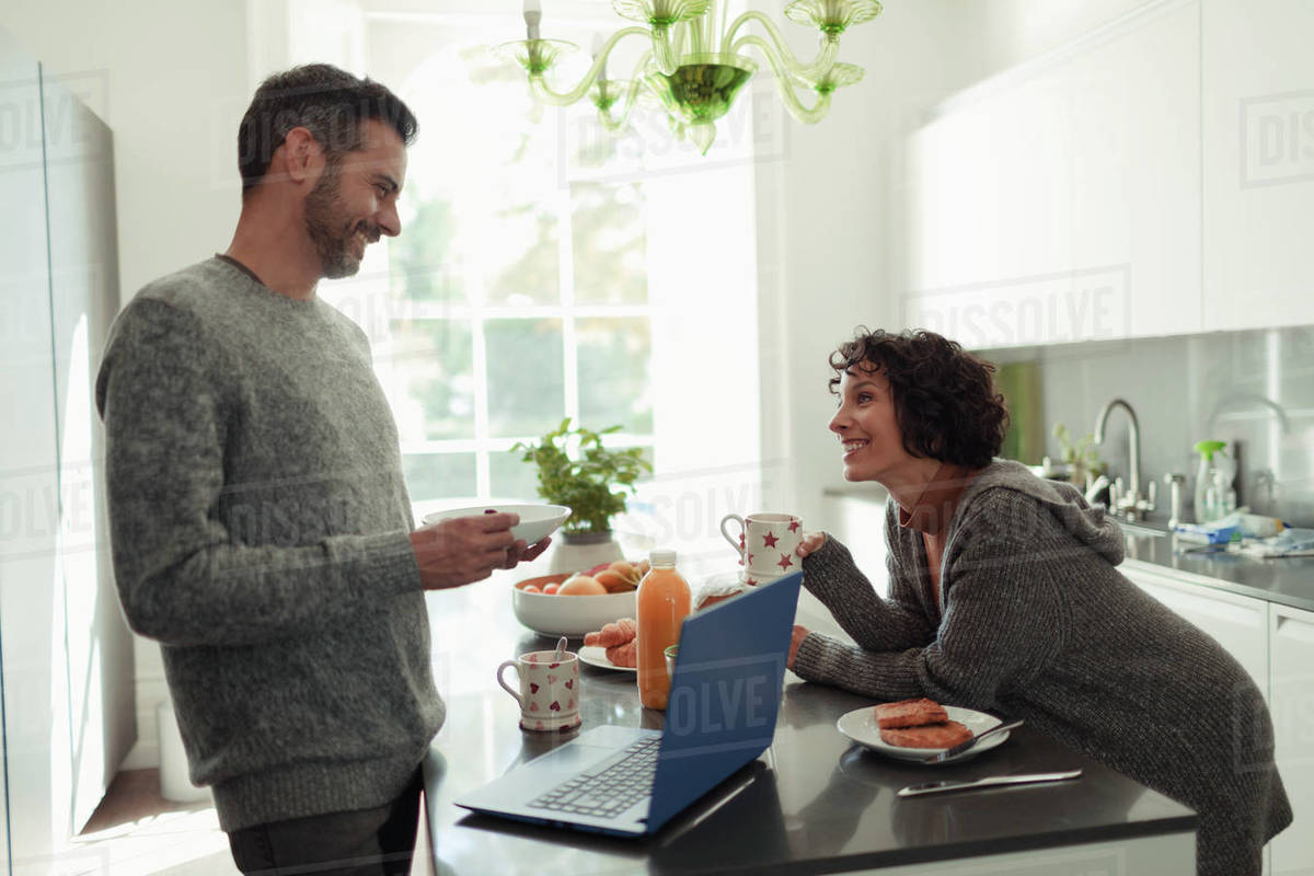 Happy couple enjoying breakfast and working at laptop in kitchen Royalty-free stock photo