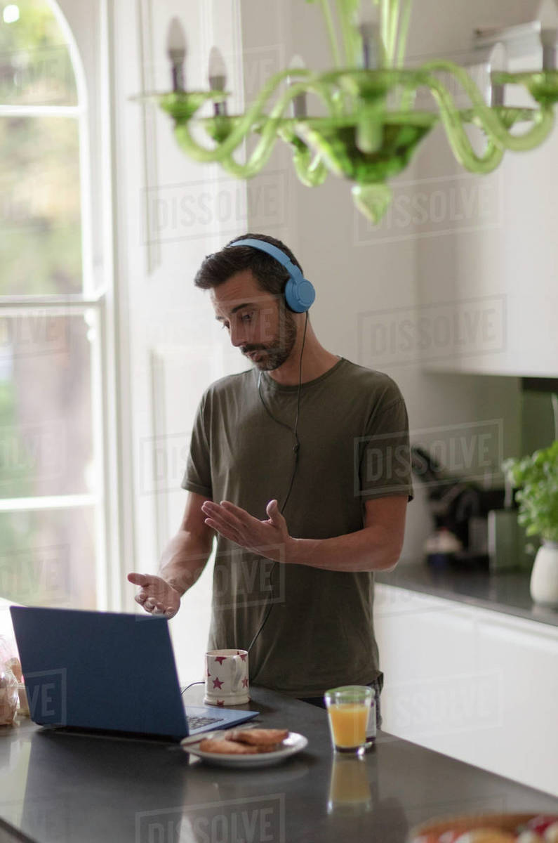 Man in headphones on video call working from home at laptop in kitchen Royalty-free stock photo