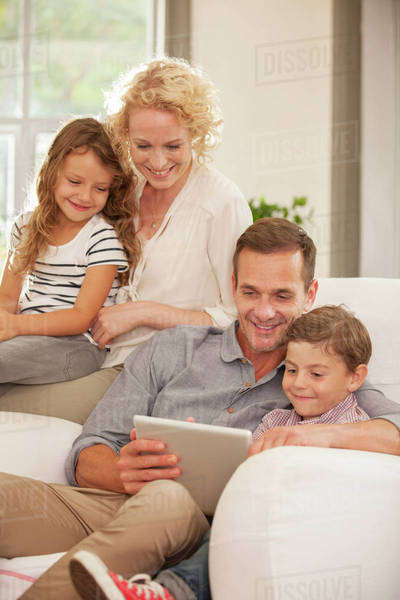 Family using digital tablet on sofa Royalty-free stock photo