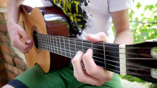 Close-up of a young man playing a guitar solo on a classical guitar, slow motion Royalty-free stock video