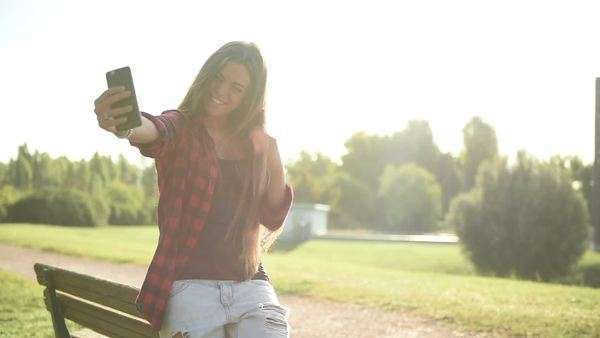 Young woman taking selfie at the park Royalty-free stock video