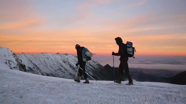 Hand-held shot of hikers walking along a snowy mountain ridge Royalty-free stock video